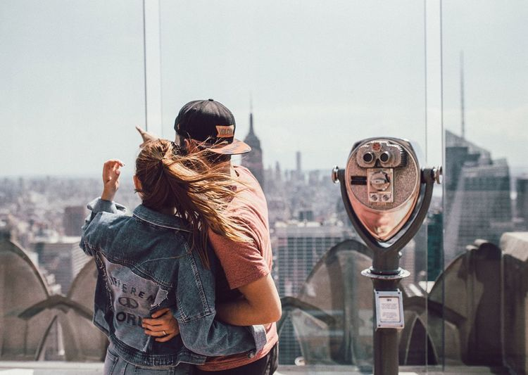 Rear View Of Couple Looking At Cityscape By Coin-Operated Binoculars
