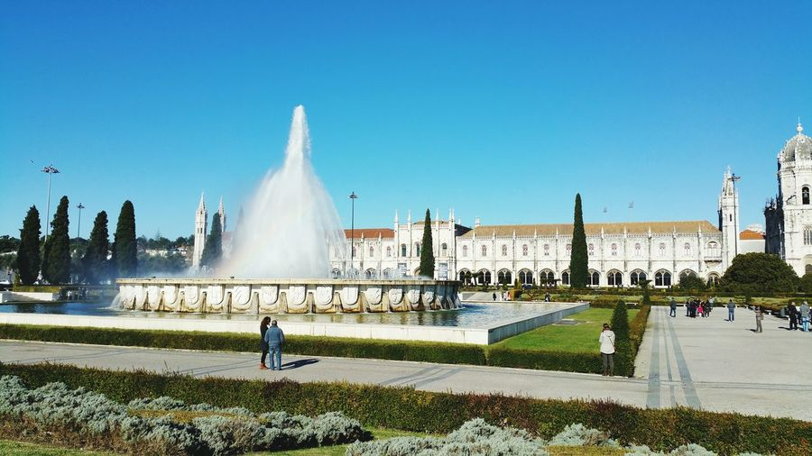 Fountain in front of mosteiro dos jeronimos against blue sky