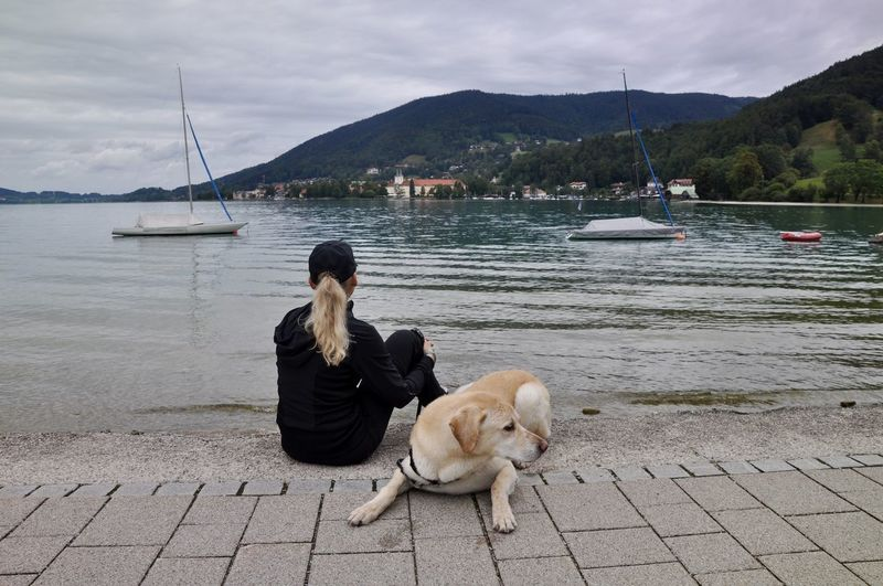 Rear view of woman with dog sitting by lake against sky