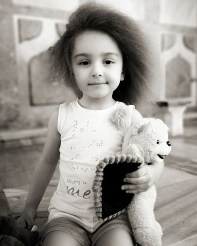 Portrait Of Smiling Cute Girl Holding Teddy Bear While Sitting At Home