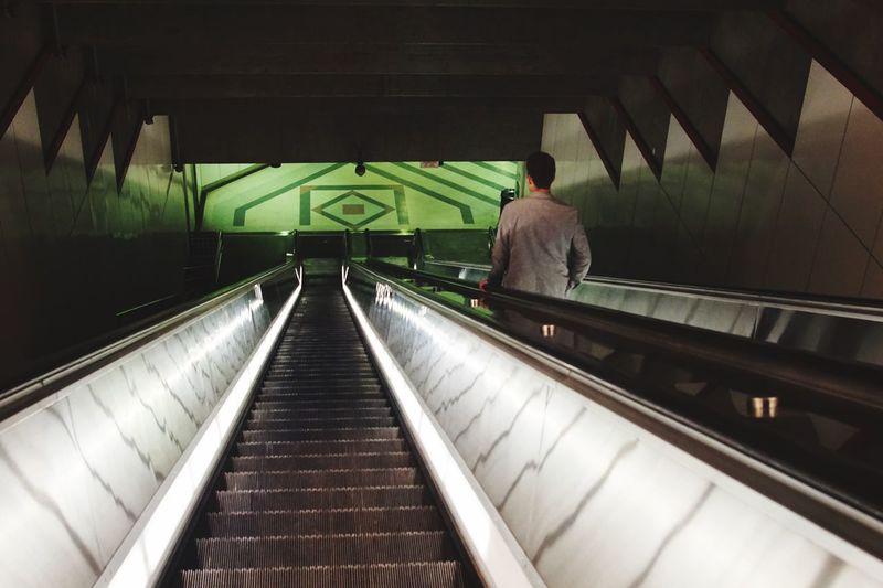 Rear view of businessman escalator in building