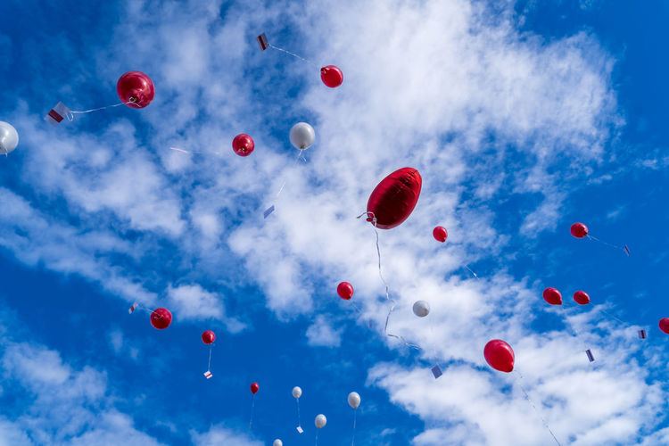 Many released flying balloons with card in blue sky - wedding balloons