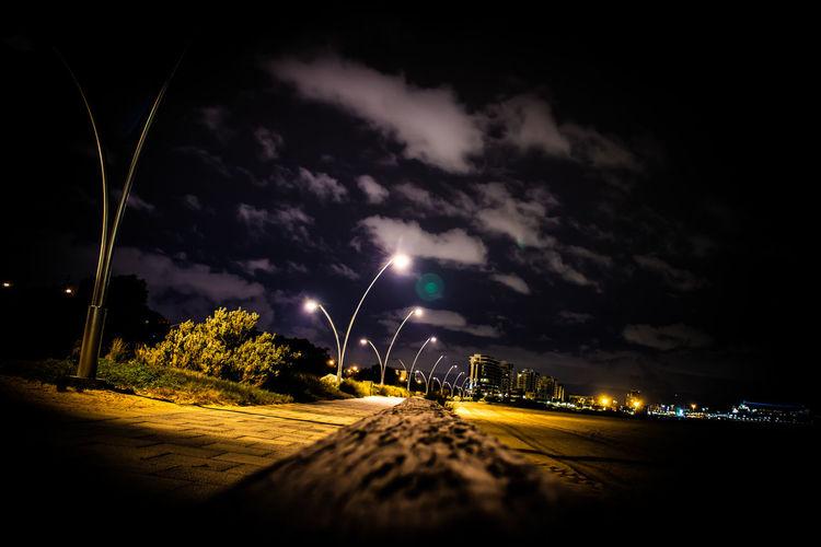 Illuminated road against dramatic sky at night