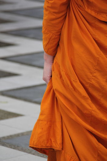 Midsection of monk wearing orange traditional clothing