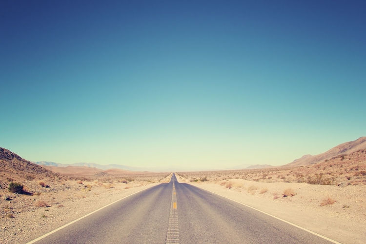 Road Amidst Desert Against Clear Blue Sky