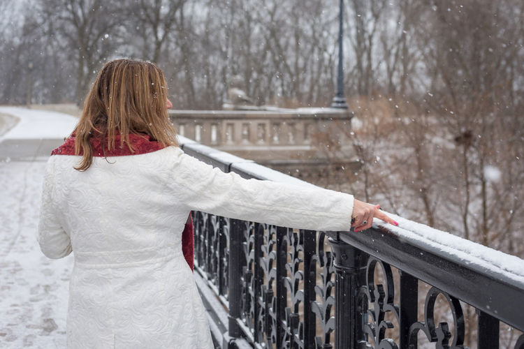 Rear view of woman touching snow on railing