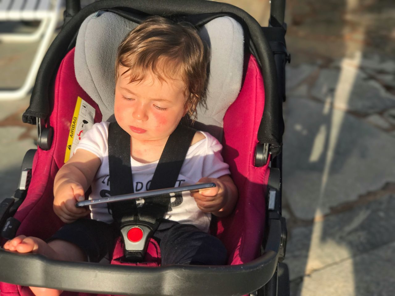 Baby With Digital Tablet In Stroller