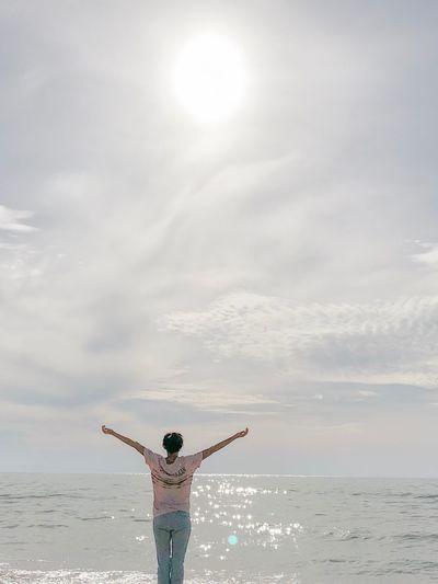 Full length of woman standing in sea against sky
