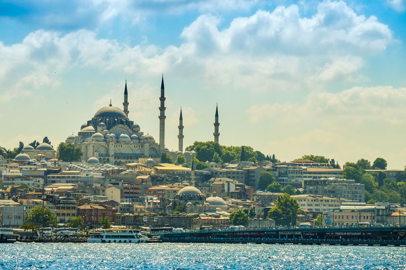 Yeni cami mosque in city by sea against sky