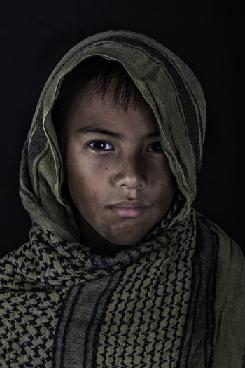 Portrait Of Boy Wrapped In Towel Against Black Background