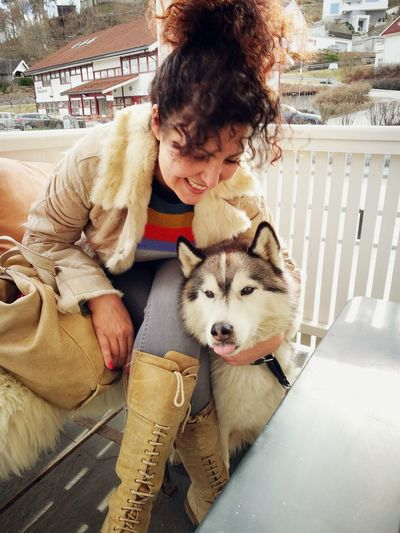 Smiling Woman With Husky Sitting By Fence Against Houses