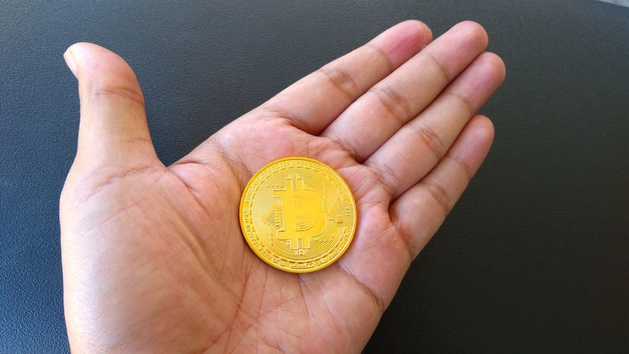 Cropped hand holding bitcoin over table