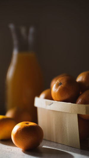 Freshly harvested clementines in basket with fresh juice on the table . healthy eating, orange