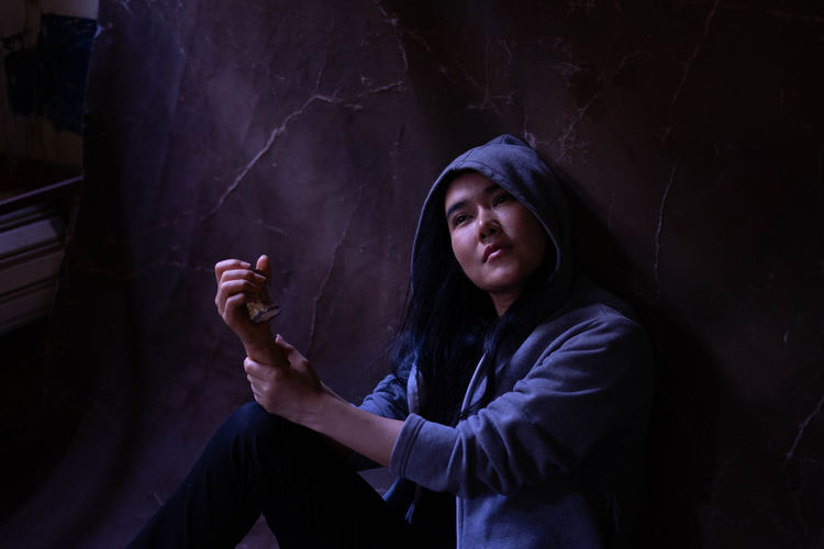 Woman wearing hooded shirt sitting against wall