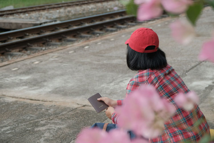 Woman using mobile phone while sitting on railroad track