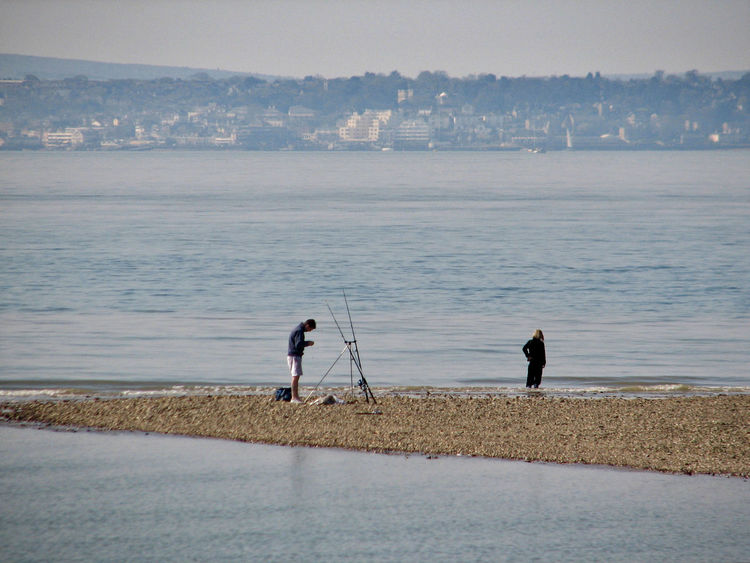 Fisherman on beach Adult Angler Architecture Beach Day Distant View Over Water Fisherman Full Length Low Tide Men Morning Outdoors People Real People Sea Shingle Spit Sky Standing Tranquil Scene Water