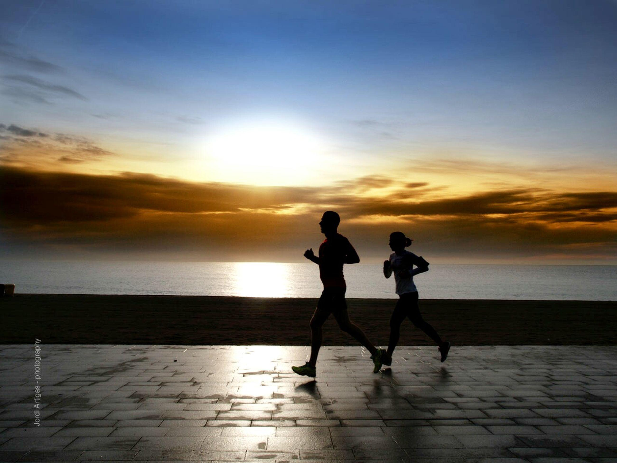 sunset, sea, horizon over water, sky, silhouette, beach, sun, water, full length, lifestyles, orange color, leisure activity, shore, cloud - sky, men, sunlight, scenics, walking, reflection