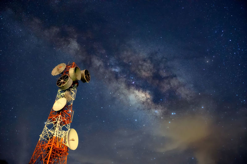 Telecommunication station at night with milky way background, transmission towers.
