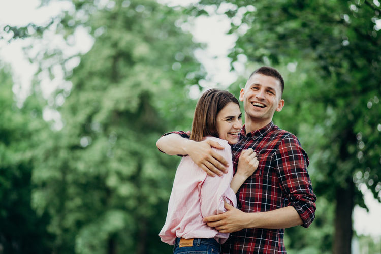 Smiling couple embracing at park