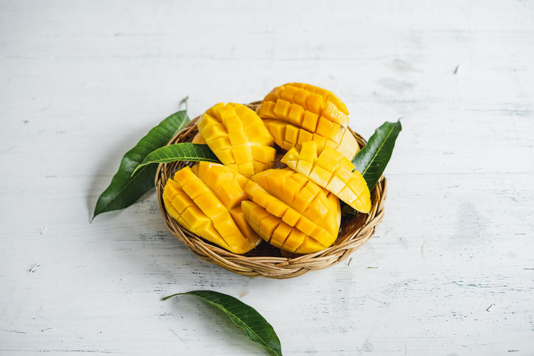 Mango in a basket Healthy Eating Table Freshness Still Life Yellow Food And Drink Wellbeing Food Indoors  High Angle View No People Close-up Vegetable Fruit Green Color Leaf Plant Part Container Wood - Material Directly Above Temptation
