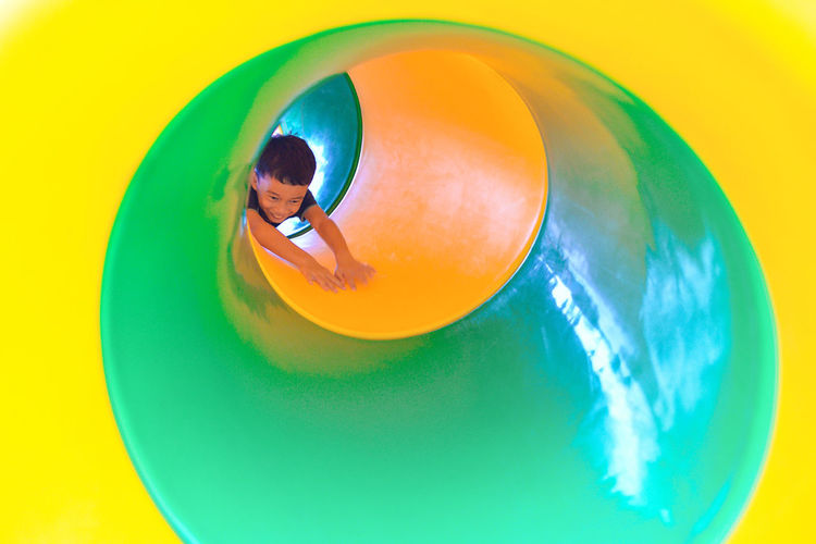 Boy Playing In Playground Tunnel