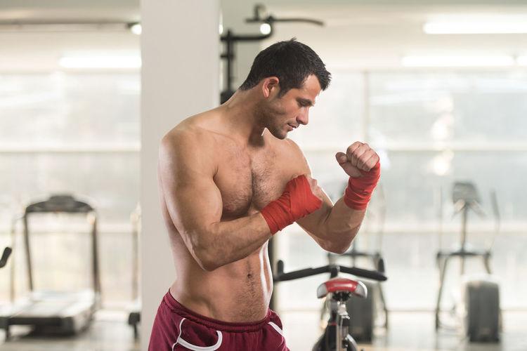 Muscular shirtless man standing in gym