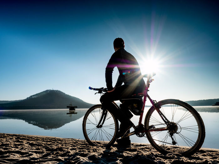 Man riding bicycle on shore against bright sun