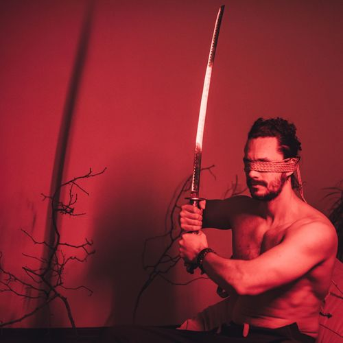 Shirtless man with blindfolds holding sword in illuminated room