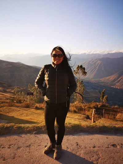Portrait of woman wearing sunglasses standing on mountain against sky