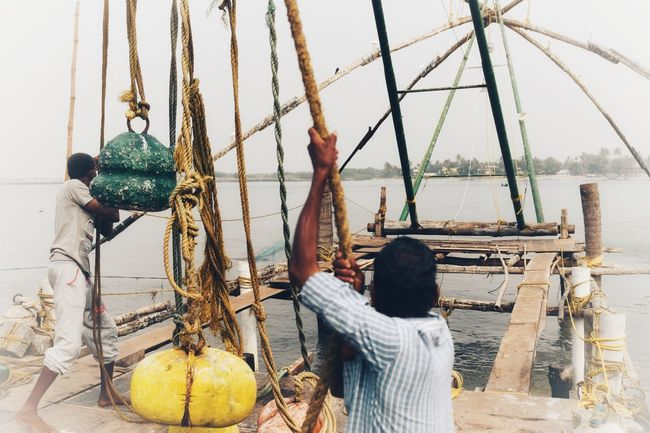 Chinese fishing nets Chinese Fishing Nets, Cochin Cochin, India Real People Men Day Lifestyles Outdoors Women Food Water Sky Adult People