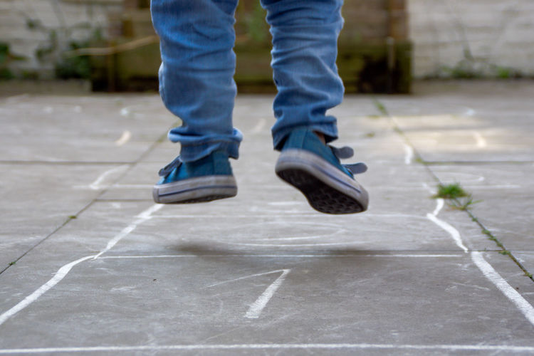 Low section of boy playing hopscotch on pavement