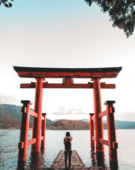 Rear view of woman standing at torii gate