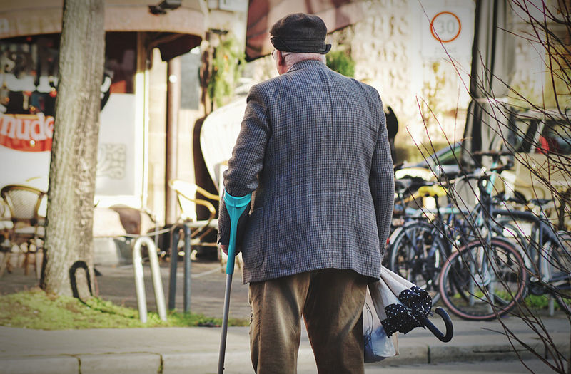 Rear view of man walking on bicycle in city