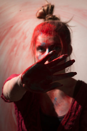Portrait of woman with powder color on palm of hand standing against wall