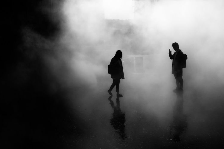Silhouette man and woman on road in foggy weather