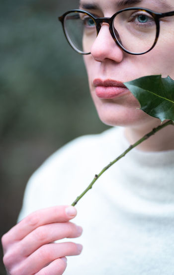 Close-up portrait of woman holding eyeglasses