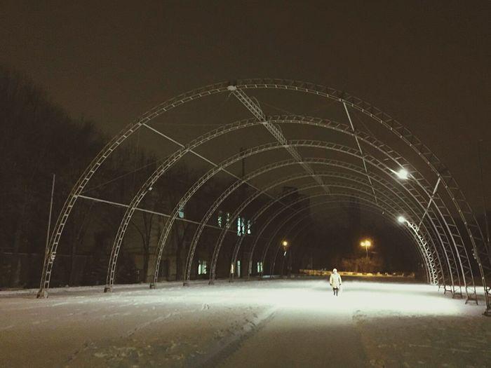 Man walking on illuminated road during winter at night