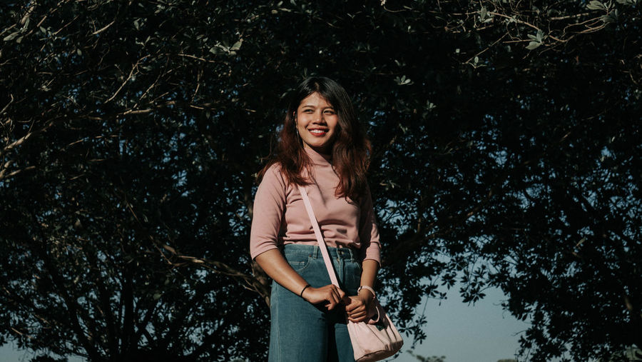 Smiling Young Woman Carrying Purse While Standing Against Trees