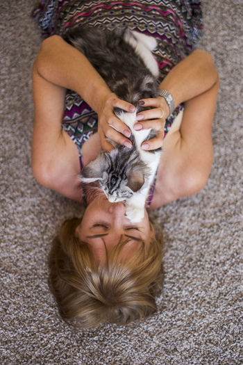Unusual and mysterious portrait for a blonde caucasian woman with her cat in front of the face. Mammal One Animal Domestic Women Adult Pets Domestic Animals Domestic Cat One Person Relaxation Hair High Angle View Blond Hair Hairstyle Front View Indoors  Purebred Cat Young Woman Resting Embracing Love Portrait Curious Beautiful People