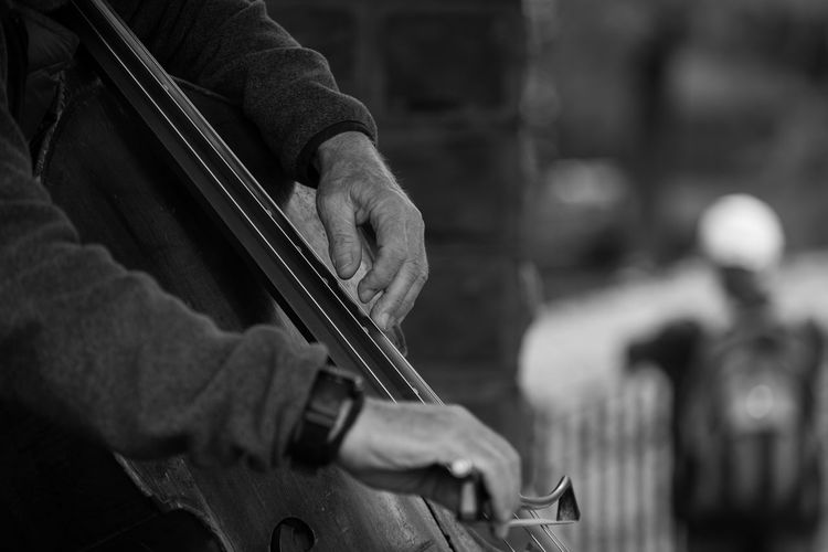 Midsection of man playing cello at central park