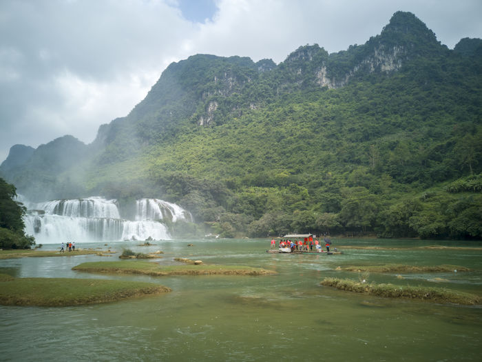 Scenic view of waterfall in forest against mountains