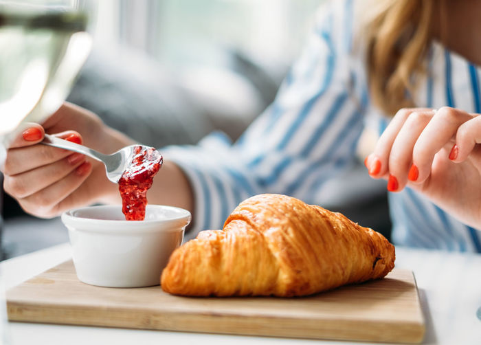 A girl eating a croissant with jam and wine Close-up Croissant Focus On Foreground Food Food And Drink Food And Drink Foodporn Freshness Holding Human Body Part Human Hand Indoors  Leisure Activity Lifestyle Lifestyles Midsection One Person People Plate Ready-to-eat Real People Red Women