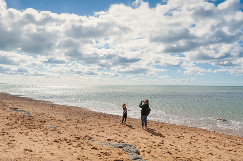 Full length of mother photographing daughter while standing on beach against sky