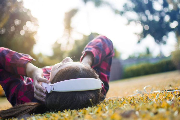 Asian trendy hipster woman lying on the grass to listen the music in headphone with smartphone for relaxing in the park city Lying Down Plant Leisure Activity Women Relaxation Grass Nature Day Casual Clothing One Person Females Sunlight Outdoors Lifestyles Surface Level Glass Listening Music Headphone Smartphone Park City Freedom