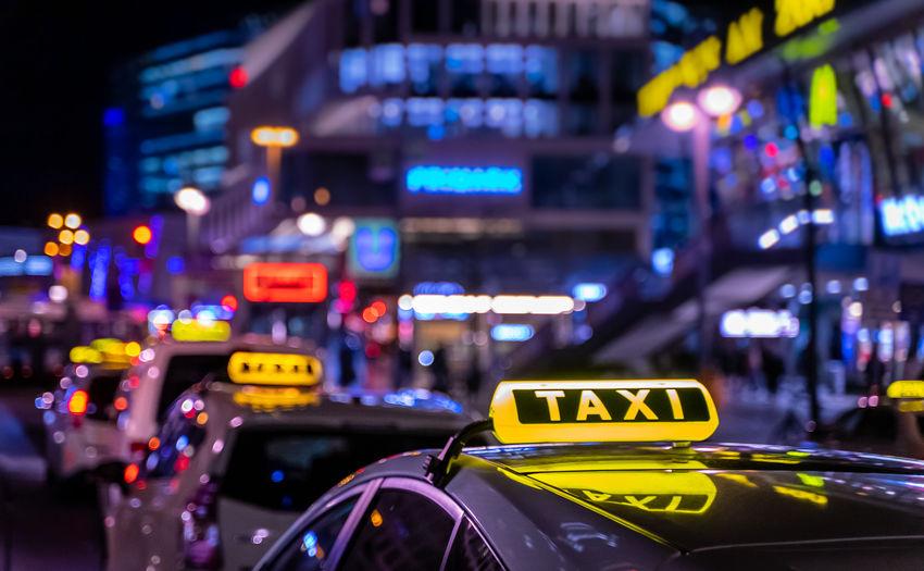 Cars on illuminated city street at night
