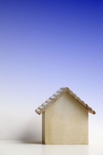 Close-Up Of Model Home On Table Against Blue Background