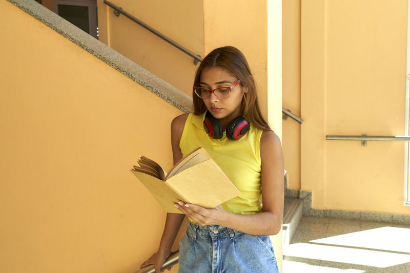 Young woman reading book against yellow wall