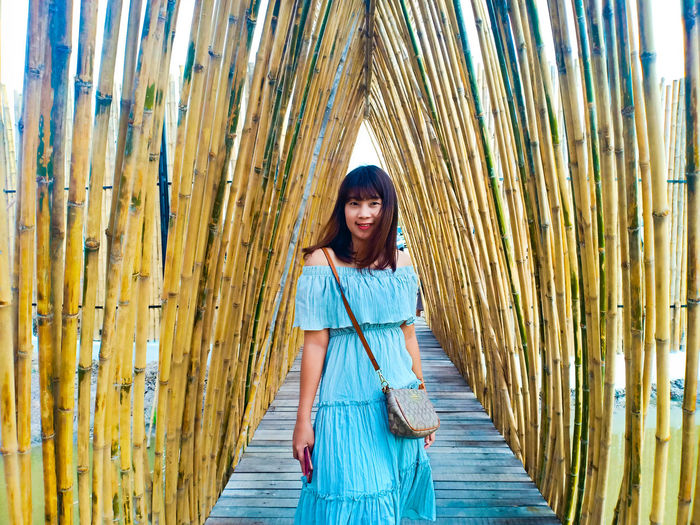 Portrait of smiling young woman standing on boardwalk amidst bamboos