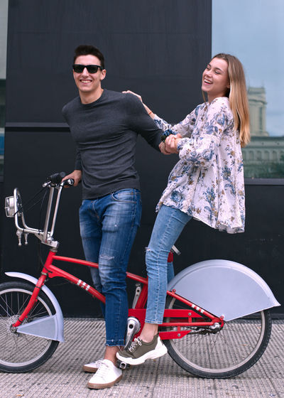 Full length of smiling young woman on bicycle