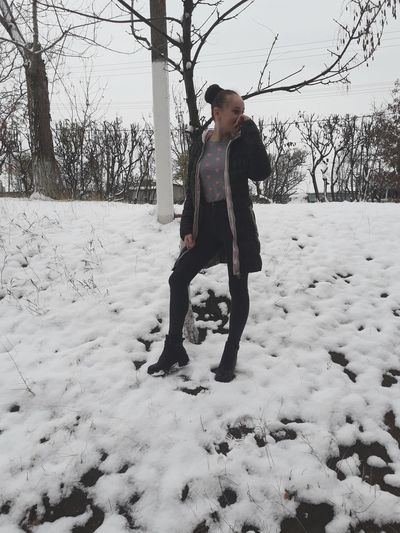 Full length of woman standing on field during winter